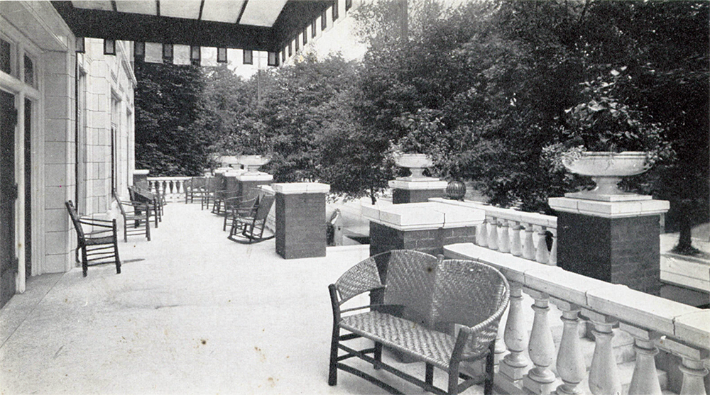 A postcard view of the Puritan Apartments showing its front porch with terra cotta facade and detailing.