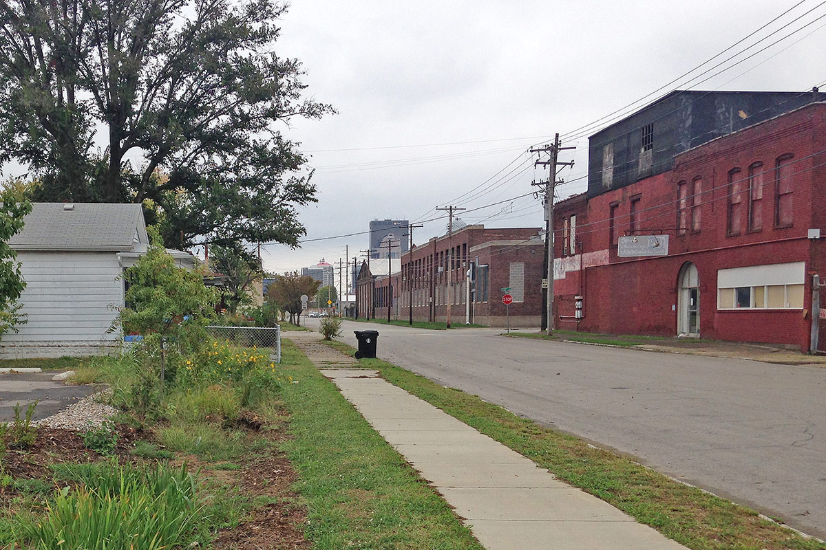 Looking east along Rowan Street with 1600 Rowan at right and a rain garden bioswale at Habitat for Humanity's ReStore at left. (Branden Klayko / Broken Sidewalk)