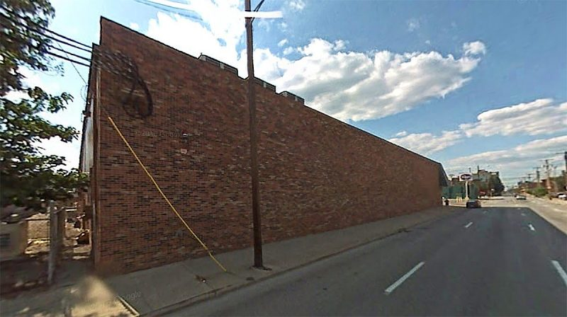 A large brick wall faces Second Street. (Google)